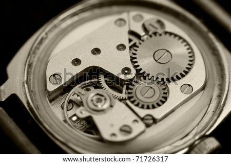an open mechanical watch, macro, sepia toning