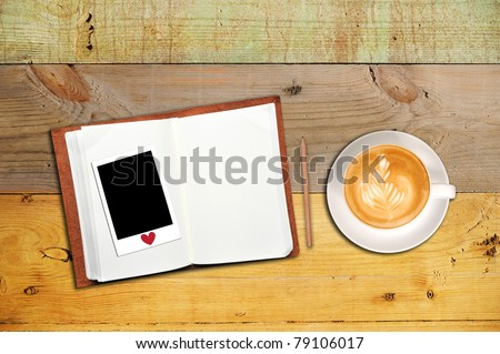 An open notebook and instant photo with cup of coffee - stock photo