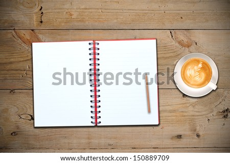 An open notebook with cup of coffee