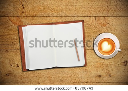 An open notebook with cup of coffee on wooden table