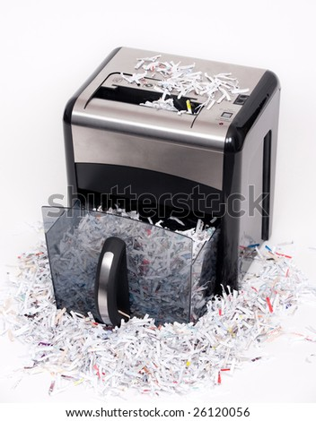 An open paper shredder with shredded paper all around - stock photo