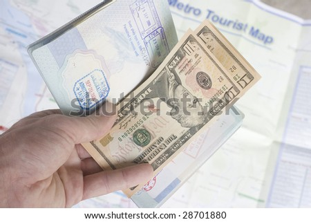 An open passport with dollars inside.  In the background is a metro tourist map.