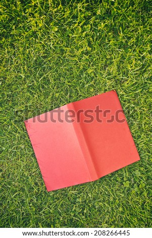An open red book lies facing down on green grass, copy space available. - stock photo