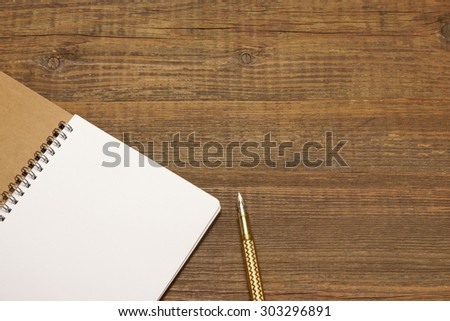 An Open Spiral Bound Notebook With White Pages And Gold Fountain Pen On The Rough Rustic Wood Table. Overhead View - stock photo