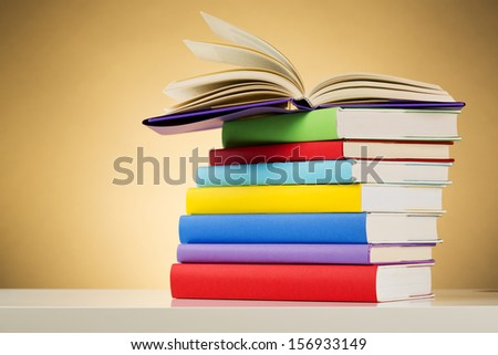 An open textbook on top of a stack of other books - concept about education. - stock photo