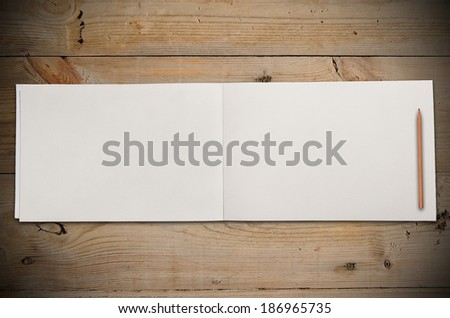 An Open Vintage Sketchbook and Notebook with Pencil on Old Wooden Table - stock photo