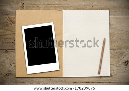 An Open Vintage Sketchbook or Notebook with pencil and blank photo on Old Wooden Table. - stock photo