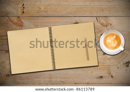 An Open Vintage Sketchbook with Pencil and a Cup of Coffee on Old Wooden Table