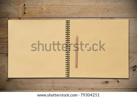 An Open Vintage Sketchbook with Pencil on Old Wooden Table - stock photo