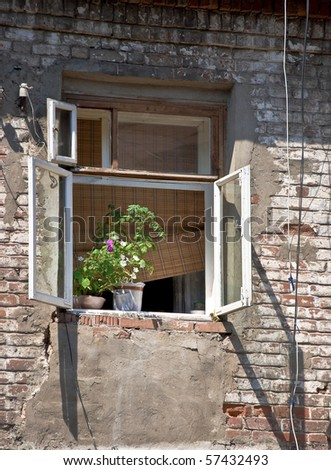 An open window in an old brick wall. On the windowsill is houseplant. Detail of the province of the court of Russia. Beggars and poor living conditions. Outdoor. - stock photo