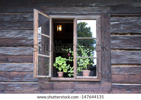 An open window of a old wooden cottage with pot plants on a window sill and and lamp inside, Roznov pod Radhostem, Czech Republic. - stock photo