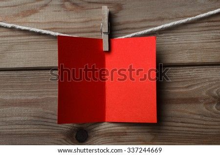 An opened, blank red greeting or Christmas card, pegged on to string against wood plank background - stock photo