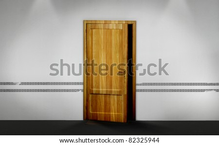 An opened wooden door with darkness spreading out, on a white wall. - stock photo