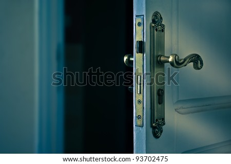 An opening door to a darker room