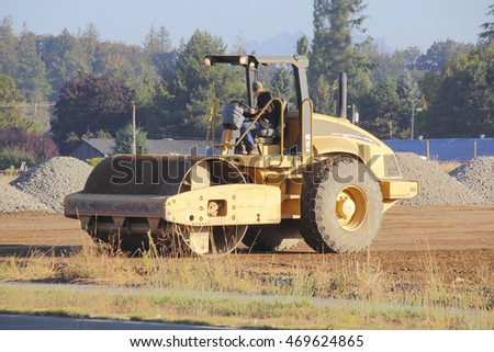 An operator backs a steamroller over dirt to prepare for a construction site/Operating a Steamroller/An operator backs a steamroller over dirt to prepare for a construction site.
