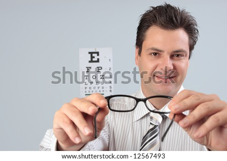An optometrist trying eyeglasses spectacles  on a customer patient.