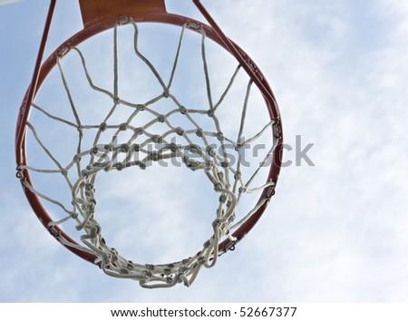 An orange basketball hoop against a blue sky - stock photo