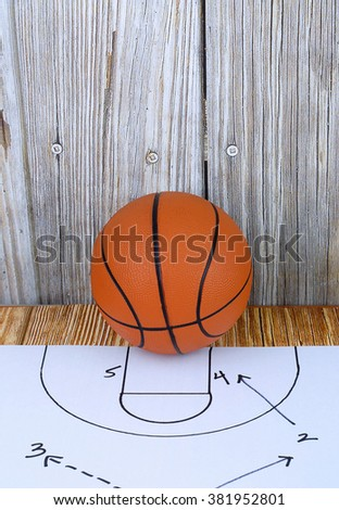 An orange basketball on a wood floor in front of a wood wall with set plans is a great image for basketball season, March Madness,or championship playoffs. Set plans are black on white. Copy space. - stock photo