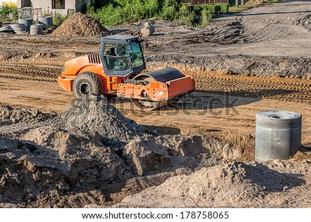 An orange construction truck smoothing the surface - stock photo