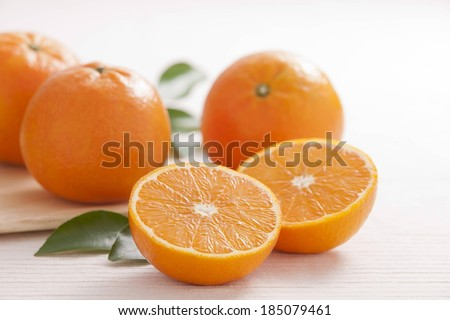 An orange cut in half and three whole oranges. - stock photo