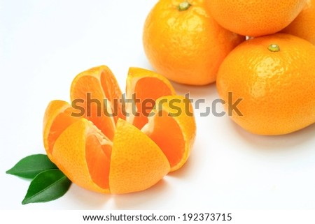 An orange cut into segments by a pile of whole oranges. - stock photo