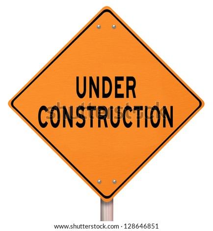 An orange diamond-shaped road sign cautions people that an area under construction lies ahead - stock photo