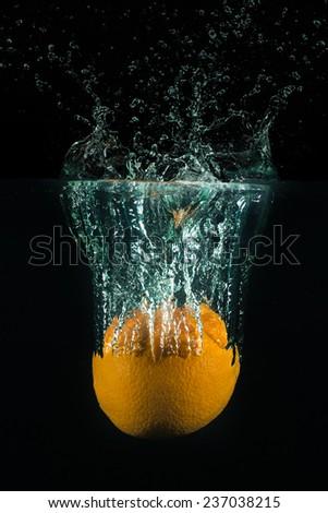 An orange drops in a water tank. - stock photo