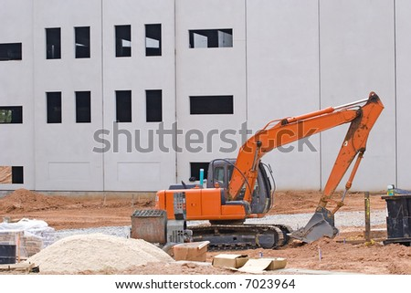 An orange front end loader at construction site with sand pile - stock photo