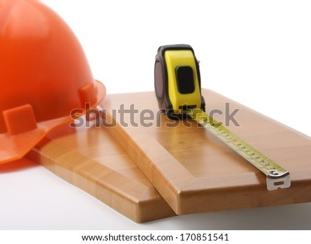 An orange hardhat with a ruler on wooden planks - stock photo
