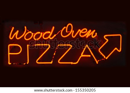 An orange neon sign reading Wood Oven Pizza - stock photo