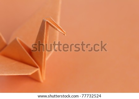 An orange paper bird on an orange background, shallow depth of field - stock photo