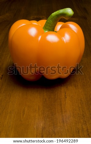 An orange pepper with a big stem sitting on a table. - stock photo