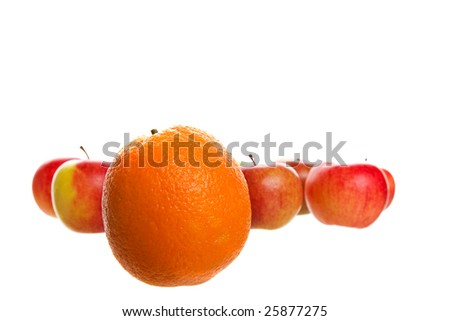An orange stands out from a crowd of apples.  Shot on white background. - stock photo