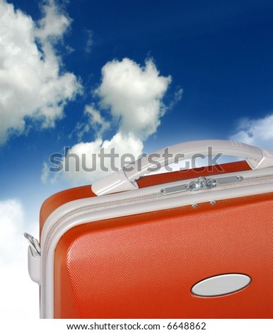 An orange suitcase sits surreal like against a backdrop of clouds and blue sky - stock photo