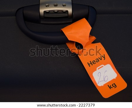 An orange tag on a heavy piece of luggage. - stock photo