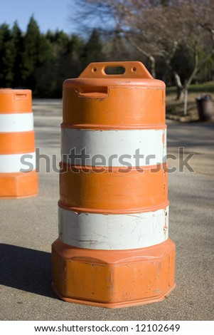 An orange traffic barrel on a small road. - stock photo