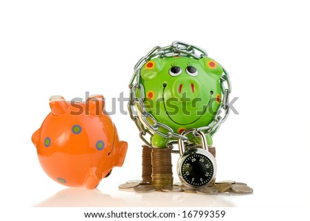 An orange upside down piggy bank and a locked green piggy bank with coins.