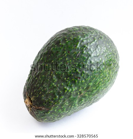 An organic unripe fresh and green avocado isolated on white background