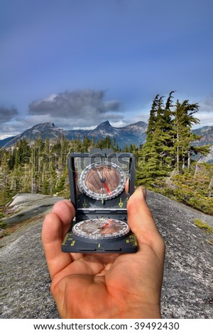 An orienteering compass is pointed towards a distant mountain summit to determine a bearing in degrees. - stock photo