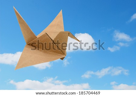 An origami bird against blue sky  - stock photo
