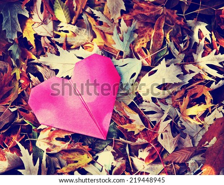 an origami heart on a pile of autumn leaves toned with a retro vintage instagram filter  - stock photo