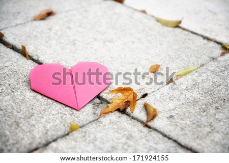 an origami heart on concrete paver blocks good for valentine's day or fall - stock photo