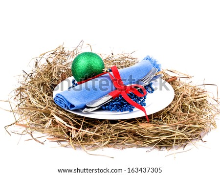 An original christmas place setting with white plates , hay and christmas ornaments - stock photo