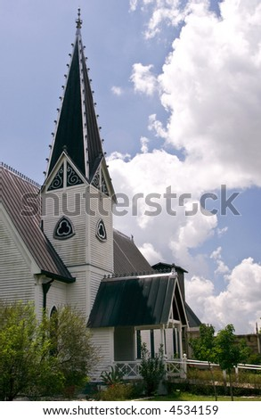 An ornate church steeple towering against a bright blue sky.