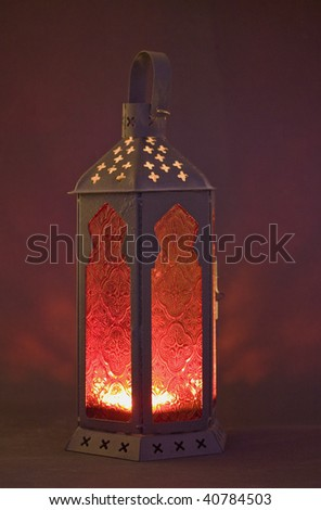 An ornate red glass lantern with a candle  burning inside - stock photo