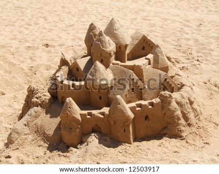 An ornate sandcastle crumbling and drying out in the sun. - stock photo