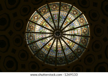 An ornate stained glass dome, viewed from below.