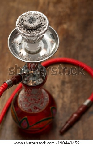 An ornate Syrian sheesha or hooka water pipe on wood table - stock photo