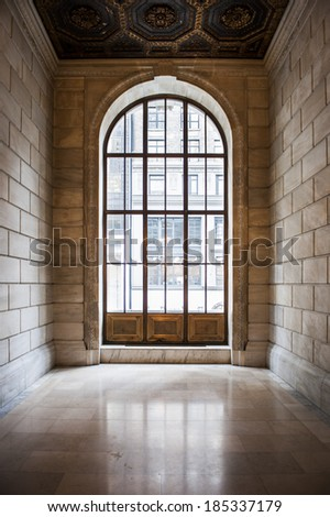 an ornate window at the end of a hallway - stock photo