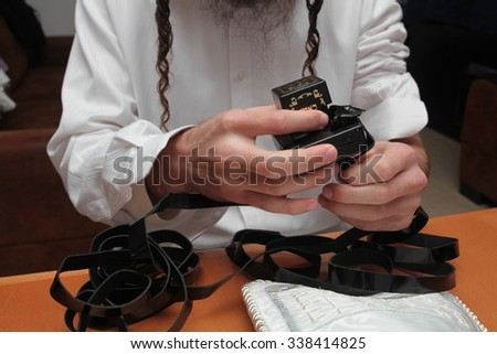 An orthodox Jew putting on his tefillin - stock photo